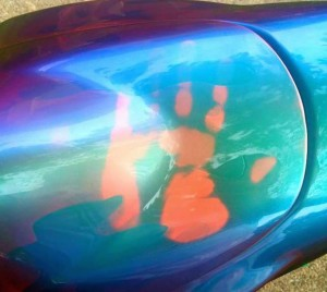 Temperature changing paint on Chameleon Super-Bike. John Haro's handprint on his thermochromic pigment painted motorcycle tank. Temperature changing chameleon!.